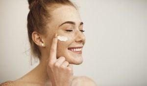 woman applying face moisturizer